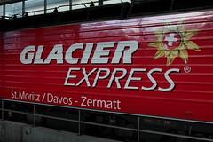 MGB Matterhorn Gotthard Bahn Lokomotive HGe 4/4 II Nr. 106 mit Taufname St. Gotthard - S. Gottardo und Werbung fr den Glacier Express am Bahnhof Disentis-Mustr in der Surselva im Kanton Graubnden - Grischun der Schweiz (chrchr_75) Tags: christoph hurni chriguhurnibluemailch chrchr chrchr75 chrigu chriguhurni dezember 2015 albumzzz201512dezember schweiz suisse switzerland svizzera suissa swiss albummgbmatterhorngotthardbahn eisenbahn bahn train treno zug mgb schweizer bahnen albumbahnenderschweiz juna zoug trainen tog tren  lokomotive  locomotora lok lokomotiv locomotief locomotiva locomotive railway rautatie chemin de fer ferrovia  spoorweg  centralstation ferroviaria