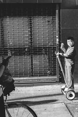 Kid on mini segway scooter eating food in Chinatown, NYC (L A Nolan) Tags: 35mm 35mmf2 50mmequiv chinatown day fuji fujifilm fujifilmxpro2 fujinon fujinonxf35mmf2 manhattan newyork newyorkcity newyorknewyork ny nyc outdoors outside people streetphotographychild thebigapple xpro2 segway scooter