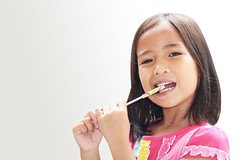 a little girl eating a lollipop (By Jan_) Tags: portrait people food white cute girl beautiful beauty face childhood smiling female laughing hair asian fun thailand person one kid holding asia child hand candy little sweet eating tail small posing happiness sugar gourmet human snack thai sit innocence stick swirl preschool cheerful lollipop enjoyment isolated nutrition refreshment caucasian