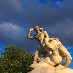 Kid playing with his pet, Jardin des Tuileries (Unvoyageur) Tags: storm paris france statue cloudy stormy minotaur jardindestuileries theseus nuageux minotaure theseusfightingtheminotaur thesee theseecombattantleminotaure