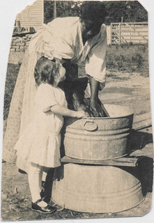 Black maid doing laundry as a smiling child watches