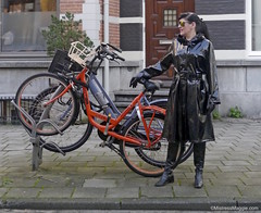 Plastic Mac Fantastic - 4/5 (Mistress Maggie dot com) Tags: woman black public leather bicycle lady female fetish standing outdoors glasses mac shiny boots coat bikes plastic gloves mature mistress raincoat rainwear pvc waterproof belted mackintosh