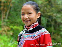2012 Southeast China Minorities (07) (Matt Hahnewald) Tags: people streetportrait china ethnicminority traditionalcostume miaopeople facingtheworld travel colour eyecontact smiling yunnanprovince yuanyangcounty closeup matthahnewaldphotography hilltribe ethnic ethnicportrait posing 43aspectratio photo image worldcultures cultural minority character personality realpeople human humanface mouth humanhead photography consent empathy emotion rapport encounter incredible portraiture portrait asian environmentalportrait travelportrait tourism traveldestination colourful horizontalformat nikond3100 nikkorafs50mmf18g primelens 50mm villager traditionalgarment colourred girl child female teeth pretty eyes bareheaded tradition