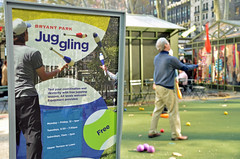 Bryant Park Juggling (thoth1618) Tags: park christmas nyc newyorkcity red orange ny newyork sign yellow december manhattan pins plastic bowling juggling juggler bowlingpins bryantpark 2015