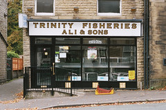 Trinity Fisheries (Peter.Bartlett) Tags: minoltax700 fastfood shopfront portra400 facade doorway film colour westyorkshire lunaphoto urbanarte urban unitedkingdom sign uk poster shopwindow kodak cafe kirklees huddersfield peterbartlett door fence analogue