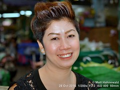 2016 Bangkok Flower Market (15) (Matt Hahnewald) Tags: facingtheworld photography photo image spectacular outstanding fantastic favourite superior excellent brilliant nikond3100 nikkorafs50mmf18g nikonsb400 flashfired primelens 43aspectratio horizontalformat closeup portrait portraiture street headshot indoor colour cultural character personality realpeople human humanhead humanface humaneyes mouth teeth lips facialexpression eyecontact consent empathy rapport encounter emotion fun mood tourism travel market pakkhlongtalat flowermarket bangkok thailand flowerarranger flowerseller flowergirl oneperson female adult maturewoman posing smiling beautiful fabulous attractive pretty stunning joyous enchanting charming hair ©matthahnewaldphotography thaismile 50mmlens fullfaceview