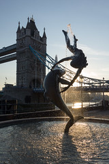 Girl with a Dolphin (Spannarama) Tags: contrejour flare sunlight sunshine lowsun london uk towerbridge bridge goldenhour blueskies fountain water dolphin sculpture shard thames river