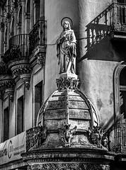 Overlooking Placa Boqueria, Barcelona (derek.dpr) Tags: placaboqueriabarcelona placaboqueria boqueria barcelona espana spain architecture architectural sculpture corner ramblas black bw bianco nero noir monochrome mono olympus omd em10