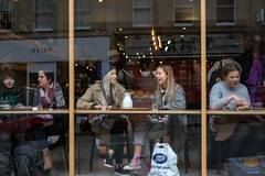 Feel Good (Silver Machine) Tags: bristol fujiholicsphotowalkbristol2016 streetphotography street streetportrait candid restaurant sitting eating girls laugh laughing expressive boots letsfeelgood bag beanie fujifilm fujifilmxt10 fujinonxf35mmf2rwr