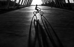 children's dreams (Georgina ) Tags: blackandwhite monochrome bicycle longshadows sunny arches boy ridingbike greece athens silhouette