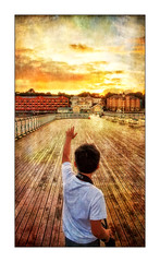 Reaching for the Sky (tina777) Tags: josh reaching sky boy child pier boardwalk sun sunset clouds colour arm camera flats apartments benches ononesoftware penarth vale glamorgan wales