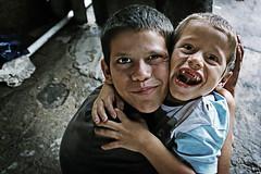 I love you so much, you know... (carf) Tags: hildren child kid boy boys natural forsakenpeople poverty brasil brazil community esperana hope social underprivileged brothers love hugs hugging embrace favela itanham smile smiling rodrigo rogerio family people