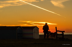 Early morning dog walker (Peter H 01) Tags: sunrise dog walker beachhuts beach hayling golden winter morning clouds