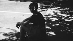 Leanne (BurlapZack) Tags: trees light shadow summer portrait bw monochrome sunglasses mono parkinglot bokeh weekend walk widescreen seat branches highcontrast shade walkabout sit summertime apartmentcomplex cinematic 169 curb 16x9 dallastx sundayfunday pack05 addisontx vscofilm panasoniclumixlx100