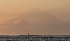 towering sufer's backdrop (Thomas Sobottka) Tags: ocean sunset sea bali orange mist canon season indonesia volcano see asia waves sonnenuntergang surfer wave dry surfing september southeast 70200 lombok indonesien vulkan agung surfen
