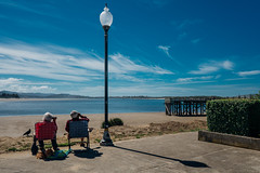 """Slow Day Here ..."", SW 51st St, Lincoln City, OR, USA (contrelamontre) Tags: beach beachlife watching binoculars dog crow foldingchairs campchairs oregon lincolncity pacific pacificcoast summer couple marriedcouple tranquility pier skyblue streetphotography street"