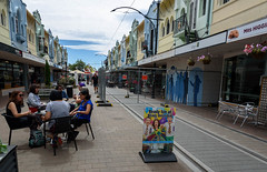 Standing Out in Purple (Jocey K) Tags: newzealand christchurch buildings city signs architecture people street sky newregentst cafes chairs tables clouds shops tramlines mural streetart painting artwork