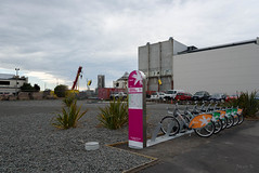 New Bikes for the City (Jocey K) Tags: city newzealand christchurch sky people urban signs cars architecture clouds buildings construction crane bikes vans cbd rebuild flax bikeshare nextbike sparkbikes