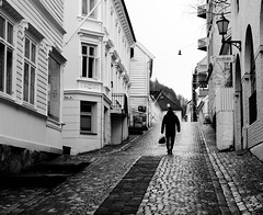 Going home (halifaxlight) Tags: norway bergen urban downtown street figure waking uphill windows lamps cobblestones woodenhouses bw