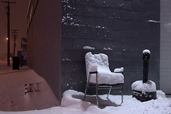 """Winter, take a seat"" (Justin van Damme) Tags: winter light orange white snow brick night dark out chair winnipeg cigarette seat telephone butt blowing pole take palette drift"