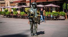 2016 - Mexico - San Luis Potosi - José Moreno Diaz (Ted's photos - Returns late December) Tags: 2016 cropped mexico nikon nikond750 nikonfx sanluispotosi tedmcgrath tedsphotos tedsphotosmexico vignetting bronzestatue bronze senorjosediazmoreno señordelaspalomas plazadearmas plazadearmassanluispotosi slp umbrellas streetscene street people peopleandpaths shadow sanluispotosiphotos