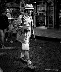 A Man and his Beer (Bart van Hofwegen) Tags: beer man walk walking sun sunshine street streetportrait hat shorts blackandwhite monochrome can drink drinking pleasure happy