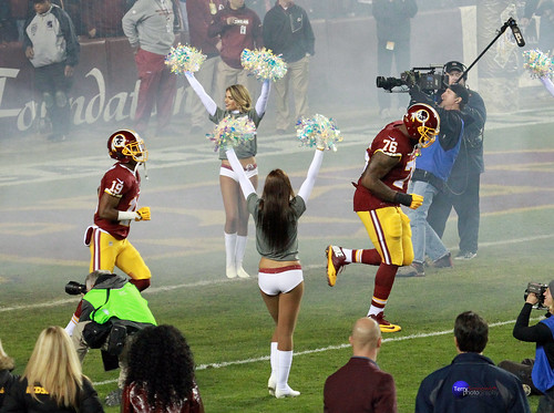 Redskins T Morgan Moses and WR Rashad Ross run onto the field through smoke and cheerleaders.