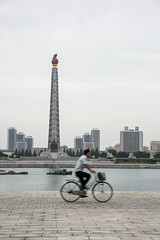 A cylcist rides alonge the Deadong River by the Juche Tower in Pyongyang, North Korea (DPRK) (tommcshanephotography) Tags: adventure asia communism dprk democraticpeoplesrepublicofkorea expedition exploring kimilsung kimjungil kimjungun northkorea pyongyang revolution secretcompass travel trekking