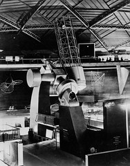 "74"" telescope on display for the Festival of Britain (Tyne & Wear Archives & Museums) Tags: astronomy space telescope observatory planets stars grubbparsons mountstromlo canberra festivalofbritain newcastleupontyne science industry blackandwhitephotograph archives digitalimage 74 reflector display 1951 mountstromloobservatory canberrraaustralia grubbparsonsltdcollection industrialheritage thomasgrubb sircharlesparsons telescopic astronomicalinstrument walkergate research suppliers futuristic surreal interesting unusual fascinating impressive east england unitedkingdom rail people observing floor wall structure beam ceiling dome noticeboard signage shapes parts glare artificiallight grain mark screen focalpoint northeast informative technology advances development construction frame"