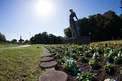Statue over the Flower Bed (nak.viognier) Tags: statue flowerbed ryokuchipark osaka 緑地公園 olympusepl3 lumixgfisheye8mmf35