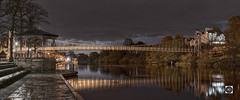 Suspended for the night. (alun.disley@ntlworld.com) Tags: queensparksuspensionbridge chester england cheshire uk night longexposure panorama bridge river clouds weather dee water nature houses trees autumn paving waterfront bandstand riverside reflections