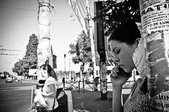 _DSC3103-2 (stimpsonjake) Tags: nikoncoolpixa 185mm streetphotography bucharest romania city candid blackandwhite bw monochrome face profile pillar advertisements girl woman phone