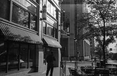 West Washington Street (patrickkuhl) Tags: street people blackandwhite west building tree film monochrome wisconsin architecture analog zeiss 35mm blackwhite washington downtown shadows kodak streetphotography d76 contax madison g1 filmcamera 45mm wisco planar 400iso contaxg1 wisc kentmere filmisnotdead kodakd76