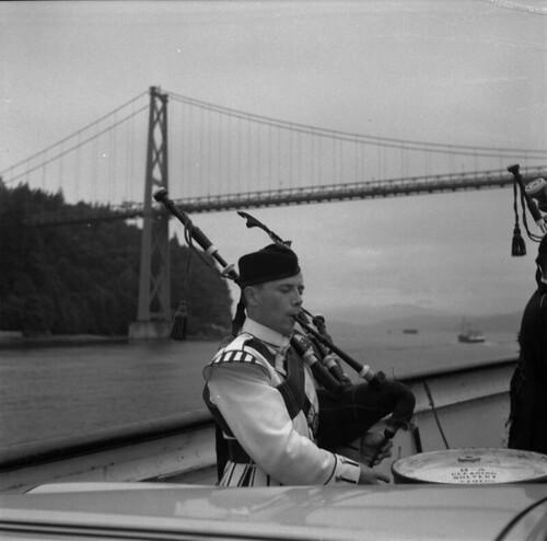 Piper on ferry passing under the Lions Gate Bridge, British Columbia /  Cornemuseur sur un traversier passant sous le pont Lions Gate (Colombie-Britannique)