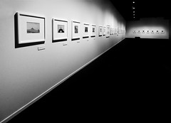Every Photograph has a History (Steve Taylor (Photography)) Tags: photograph gallery label art picture museum wall carpet light lamp monochrome blackandwhite monotone contrast stark newzealand nz southisland canterbury christchurch city perspective bench seat shadow exhibition photography