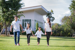 Beautiful family portrait smiling outside their new house