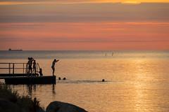 Going for a swim at Sunset (Infomastern) Tags: skanr cloud hav himmal moln mnniska people sea silhouette siluett sky solnedgng sunset water