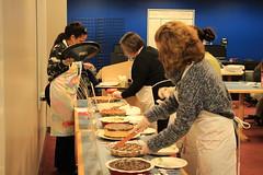 Servers start cutting each pie to prepare for the judges blind taste test.