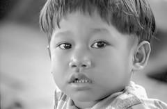 Laos : portraits #11 (foto_morgana) Tags: analogphotography analogefotografie asia boy child childhood eyes ilfordxp2 indochina jeugd jeune jeunesse jong juventud kid laos lightroom nikoncoolscan outdoor people photographieanalogue portrait portret travelexperience vuescan young youth