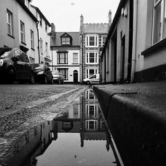 Stryd yr Undeb, Aberystwyth (Rhisiart Hincks) Tags: aberystwyth ceredigion reflexin adlewyrchiad islada adsked reflection faileas pwll poull achuimrigh kembra wales cymru kembre gales galles anbhreatainbheag paysdegalles galesherria kimrio  uells  velsa velsas     walia   duagwyn gwennhadu dubhagusgeal dubhagusbn zuribeltz czarnobiae blancinegre blancetnoir blancoynegro blackandwhite  bw zwartenwit mustajavalkoinen crnoibelo ernabl schwarzundweis feketefehr melnsunbalts juodairbalta negruialb siyahvebeyaz rnoinbelo