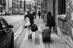 Movin' (Geoff France) Tags: street blackandwhite monochrome manchester mono northernquarter north streetphotography gritty backpack suitcase manchesternorthernquarter