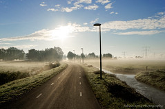 A road to go (Johan Konz) Tags: overflooding sunshine morning mist rural road grass fields watercourse serene atmosphere zunderdorp waterland netherlands outdoor misty water blue sky white clouds nikon d90