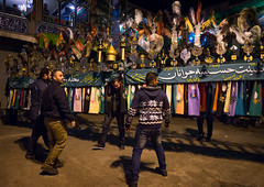 an iranian man carries an alam is helped by shiite muslim mourners to keep his balance on ashura, the day of the death of hussein, Golestan Province, Gorgan, Iran (Eric Lafforgue) Tags: people colour male men festival metal horizontal night religious outdoors athletic colorful iron mourning iran bright muslim islam traditional religion decoration performance arts feathers middleeast culture persia parade ostrich celebration shia ritual muharram ashura effort procession colourful calligraphy script tradition abundance hussein strenght alam iman fourpeople shiite ashoura elaborate hussain gorgan 4people golestanprovince 30sadult persiangulfstates  onlymen  16428 husayn colourimage  iro shiism  alaam westernasia
