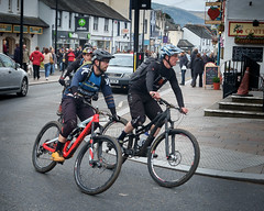 Boy Racers. Cyclists in Keswick Town Centre. (James- Burke) Tags: bikes cycling cyclists fuji fujixpro1 mountainbikes people racing speed street streetincolour traffic photography candid streetphotography candidphotography keswick cumbria towncentre trafficlights shops fujixf1855