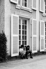 taking a rest during sightseeing (mathias-erhart) Tags: salzburg tourist tourists person people woman women girl girls window windows shutter shutters blinds blackwhite monochrome