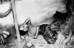 An ill woman lying outside her hut
