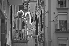 Reading on the balcony (Santini1972) Tags: nikonflickraward sunday neighborhood blackandwhite catalonia ripoll nikon35mm18 people oldwoman book street windows black white balcony nikond5100 clothes reading