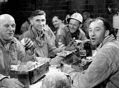 Workmen of the Asbestos Corporation enjoying their lunch at lunchtables provided by the corporation / Des ouvriers de la Société Asbestos au moment de leur repas du midi, assis à des tables fournies par l'entreprise
