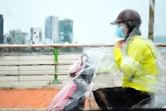 Wet ride (Roving I) Tags: women lifestyle rain weather rainwear plastic helmets bridges hanriver danang vietnam facemasks travel transportation blur impressions mood atmosphere