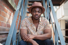 Oche (Larry Atanasov) Tags: north america toronto artist music musician black african american canadian downtown bricks fire exit bokeh portrait environmental natural candid shoot photoshoot hat floral shirt short sleeve